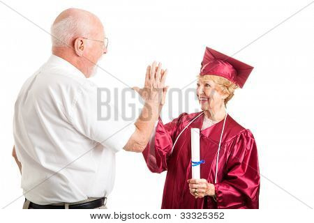 Senior woman graduating from high school gets a high five from her husband.  Isolated on white.