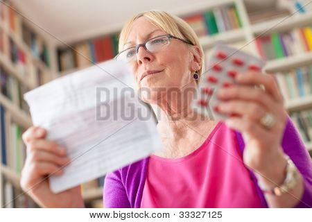 Senior Woman With Medication Pills And Prescription