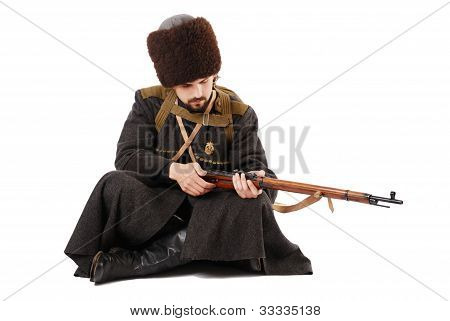 Russian Cossack Inspecting A Rifle In Sitting Position. The Living History.