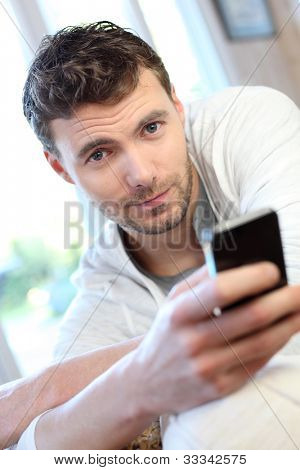Young man using mobile phone to send short message
