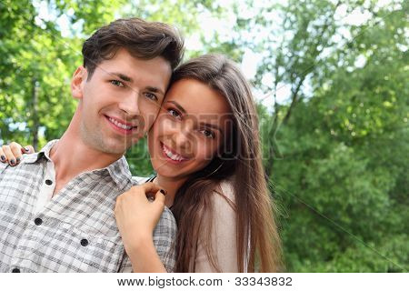 Smiling young man and woman stand in park; woman holds on shoulders of man; green trees and sunny day