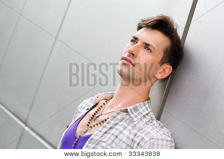 Young beautiful pensive man stands near gray wall and looks up