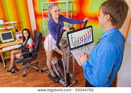 Office portrait of beautiful businesspeople doing exercise at their workplace