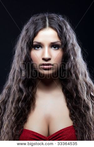 Young beautiful serious girl with curly hair