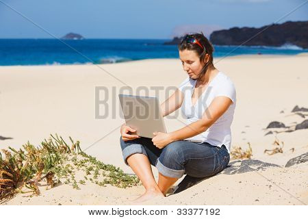 Woman on the beach with laptop computer