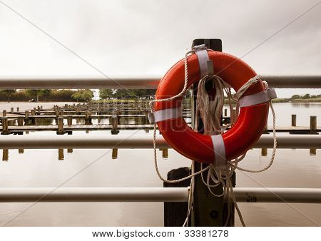 Red Life Belt In Front Of Empty Boat Dock Harbor