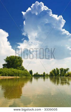 A Cloud Against A Backdrop Of Blue Sky. Landscape By The River