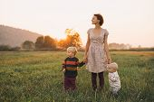 Young Mother With Children In Sunlight At Sunset On Nature Outdoors. Parents And Kids In Meadow In E poster