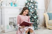 Reading Days Of Christmas. Cute Little Girl Read Book At Christmas Tree. Adorable Small Child Enjoy  poster