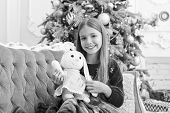 Best Christmas Toy. Little Girl With Cute Bunny At Christmas Tree. Small Girl Hold Rabbit Toy. Littl poster