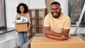 moving, repair and real estate concept - happy african american couple with stuff in cardboard boxes poster