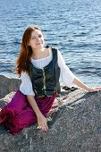 stock photo of shepherdess  - Medieval woman sitting on a big rock near the sea - JPG