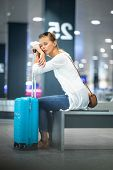 Young woman with her luggage at an international airport, waiting for her luggage to arrive at the b poster