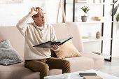 Displeased Senior Man With Alzheimer Disease Holding Photo Album poster