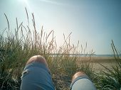 First-person View Of A Man Relaxing, Enjoying View Over The Beach With Wild Grasses. Legs In Jeans O poster