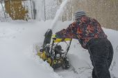 Man Operating Snow Blower To Remove Snow On Driveway. Man Using A Snowblower. A Man Cleans Snow From poster