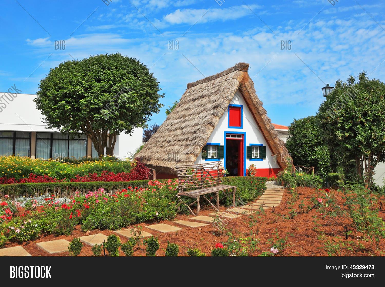 Encantadora Casa De Campo Blanco Con Un Techo De Paja Y
