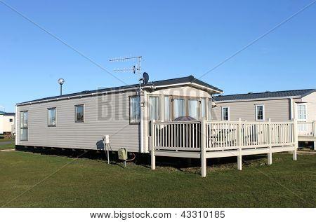 Modern caravan home in trailer park with blue sky background.