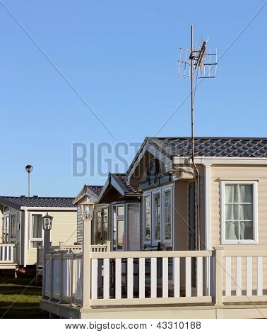 Side view of modern caravan homes on trailer park, summer scene.