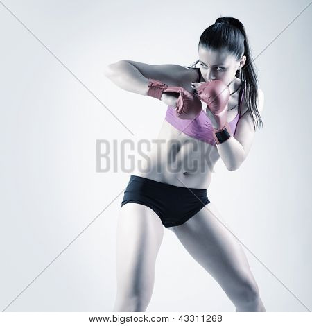 sport young woman with combativity gloves going to fighting, active fitness girl, studio shot