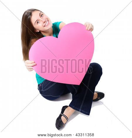 portrait of attractive happy smiling teen girl with big pink heart, love holiday valentine symbol over white background