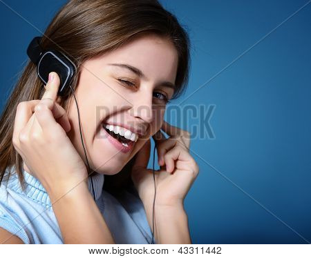 attractive teen girl listening to music on headphones and winking, portrait over blue background with copy space