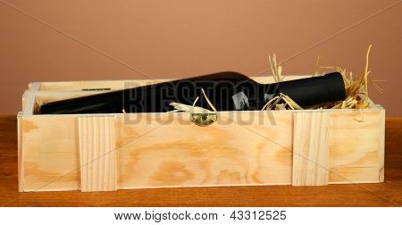 Wine bottle in wooden box on wooden table on brown background