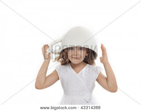 happy pretty  little girl with big cup on her head isolated on white studio shot looking at camera smiling