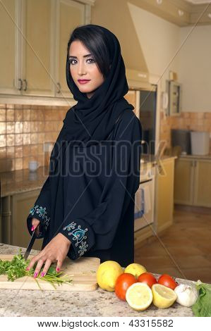 Arabian lady wearing hijab cutting veggies in the kitchen