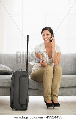 Happy Young Woman In Living Room With Travel Bag Talking Mobile Phone
