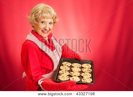 Sweet adorable grandmother holding a pan of freshly baked chocolate chip cookies.   Photographed over red background with room for text.