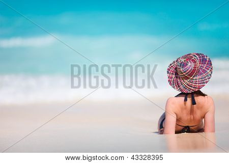 Back view of a young beautiful woman relaxing at tropical beach