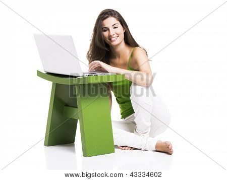 Beautiful woman sitting in the floor working with a laptop, isolated over a white