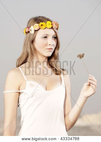 Beautiful young woman in a meadow wearing a crown of flowers
