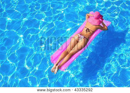 Sexy Girl auf einer Matratze im Pool oder im Meer treiben
