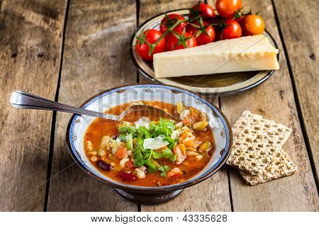 Minestrone vegetable soup with parmesan cheese .