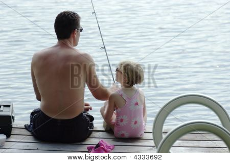 Father And Young Daughter Fishing