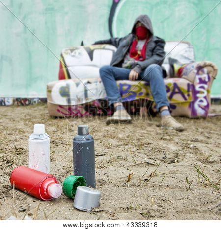 Spray paint cans on the sand in front of a large spray painted graffiti wall, with an artist, posing on a tagged couch, out of focus