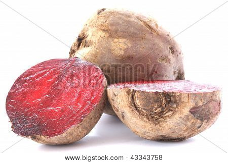 Two whole beetroots also called red beet on white background one cut in half