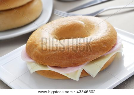 closeup of a plate with a bagel stuffed with cheese and ham on a table