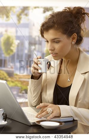 Attractive young businesswoman using laptop and drinking coffee outdoors.