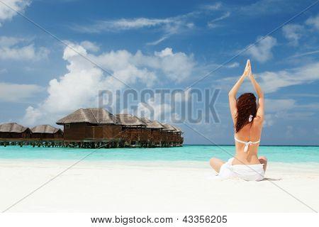 woman doing yoga exercises on the beach