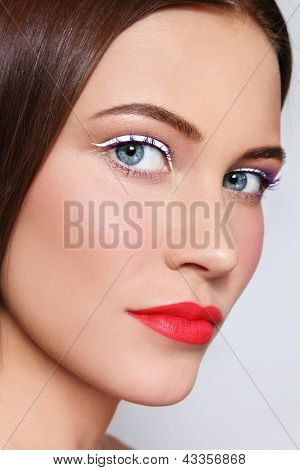 Close-up portrait of young beautiful woman with stylish white eyeliner and coral matte lipstick