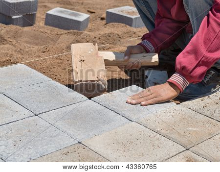 The Worker Paves A Stone Path