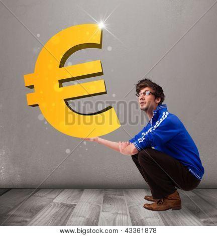 Boa aparência jovem rapaz segurando um grande sinal de euro ouro 3d