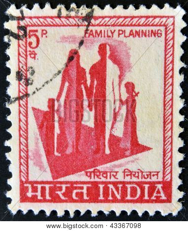 A stamp printed in India shows a symbol of family planning campaign