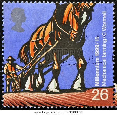 stamp printed in Great Britain dedicated to Millennium shows mechanical farming