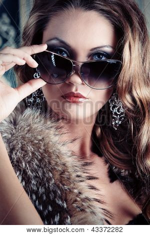Beautiful glamorous woman posing in fur and sunglasses at studio.