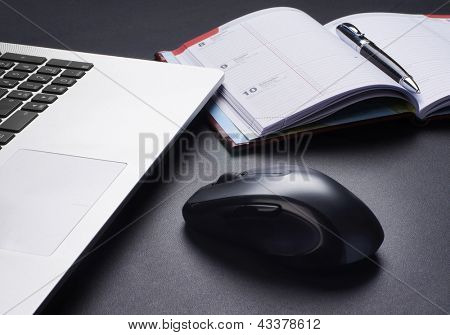 Laptop, mouse and the diary on the table