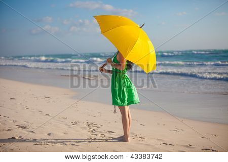 young woman with yellow umbrella on the beach